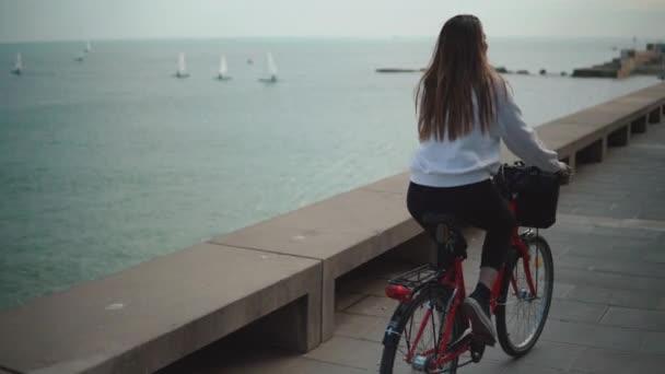 Žena jedoucí na kole podél pláže v letní době