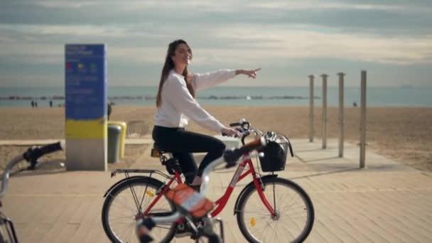 Žena jedoucí na kole podél pláže písek na letní čas