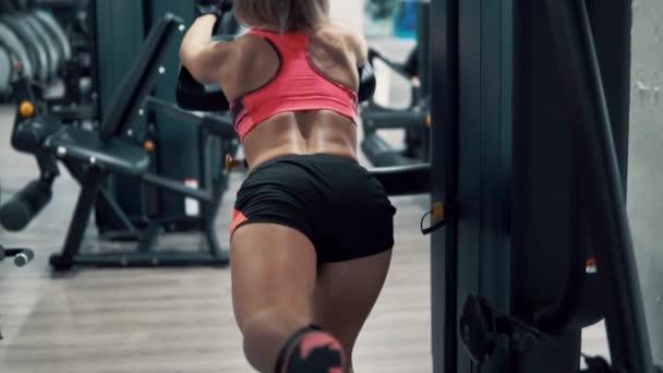Žena, která dělá cvičení pro nohy a hýždě svalů v tělocvičně