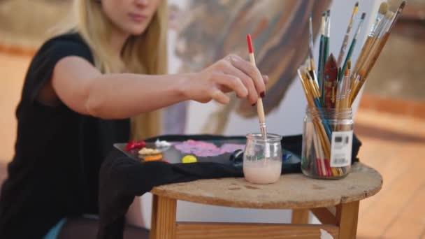 Fiatal nő festék művész rajz otthon tető. Bulldog a nagy vászon képe. Szabadban slowmotion art