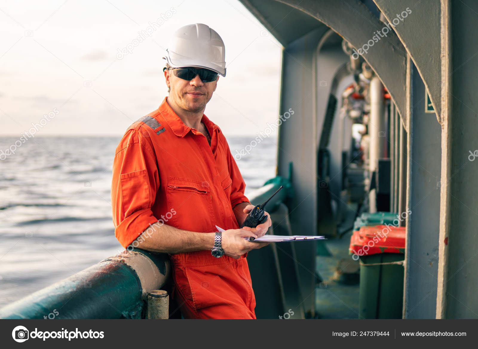 Deck Officer on deck of offshore vessel holds VHF walkie-talkie