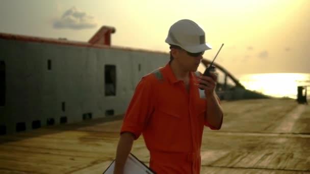 Offizier an Deck des Offshore-Schiffs hält Walkie-Talkie-Radio