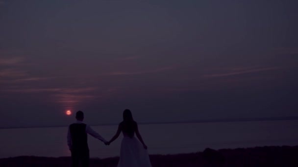 loving couple - young groom and beautiful bride at sunset
