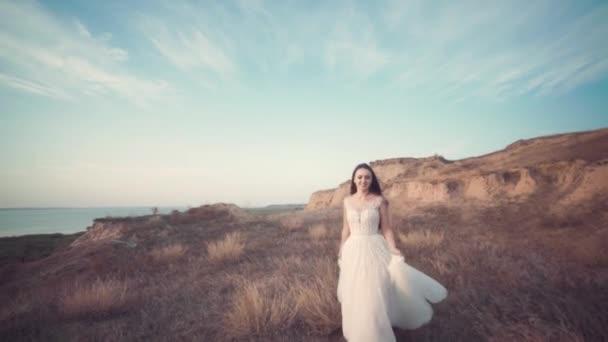 Běžící nevěsta v úžasné dlouhé šaty krajinou.
