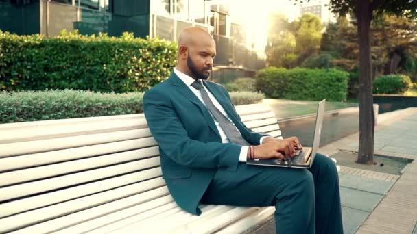 Indický podnikatel s notebookem v modrém obleku poblíž kanceláře