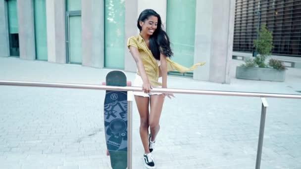 hezká atletická dívka jezdí na longboardu v moderním městě