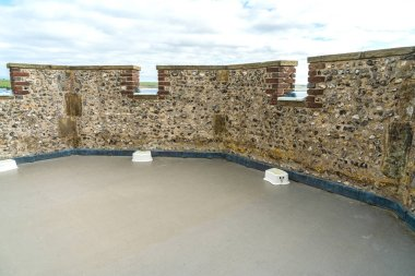 Top floor, view of a line of battlement in the Lewes Castle, East Sussex county town with small chair for visitor to see landscape outside of the Castle.