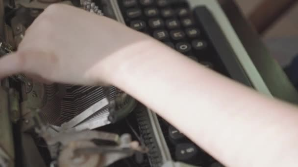 Little six-year-old boy studies the work of an old typewriter. Close-up hands