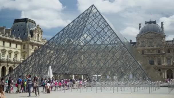 Line to ticket office of Louvre museum. Pyramids, fountain. Tourists on square