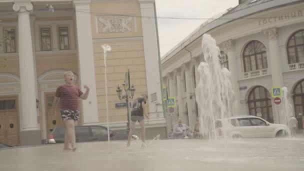 Happy boys play in fountain near the Gostinniy Dvor in Moscow