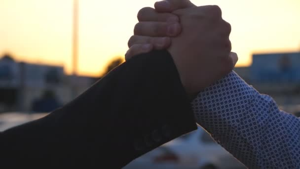 Two business men having firm friendly handshake outdoor with sun flare at background. Shaking of male arms outside. Friends meet and shake hands in the city background. Close up Slow motion