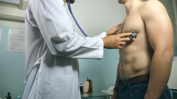Medic ellenőrzése mellkasi sportos srác az irodájába, a kórházban. Orvos vizsgálata fiatal férfi beteg sztetoszkóp. Orvosi munkavállaló hallgató szívverés az ember. Közelről