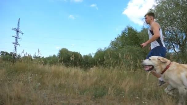 Mladý muž běží venkovní se svým psem. Labradorský nebo zlatý retrívr, běhání s paničkou samec v přírodě. Zdravý aktivní životní styl. Slow motion boční pohled
