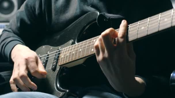 Zblízka prsty kytaristy na řetězce. Pánská zbraní hraje sólo rockové hudby. Ruce muže hudebník hraje na elektrickou kytaru. Krásné černé pozadí v ateliéru. Zpomalené Detailní záběr