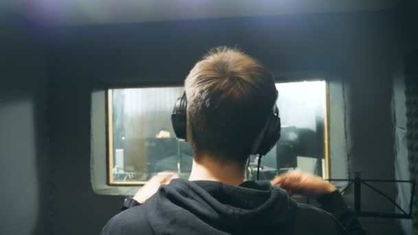 Male singer in headphones singing song at sound studio. Unrecognizable young man emotionally recording song. Working of creative musician. Show business concept. Slow motion Rear back view