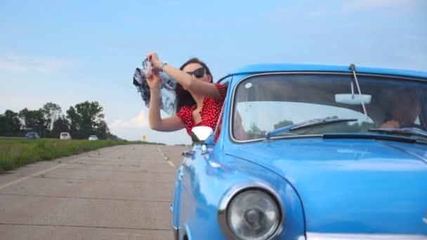 Šťastná dívka s šátkem v ruce vyklonil se z okna veteránem a užívat si výlet. Mladá žena při pohledu z okna stěhování starých retro auto na slunečný den. Cestování a svobodu koncept. Detailní zpomalené