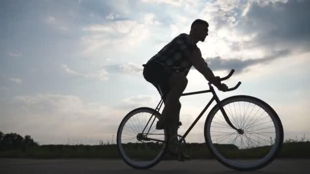 Silueta mladík na koni na vintage kolo s krásného západu slunce na obloze v pozadí. Sportovní chlap na kole v zemi silnici. Mužské cyklistu jedoucího pevné ozubené kolo. Zdravý aktivní životní styl Closeup