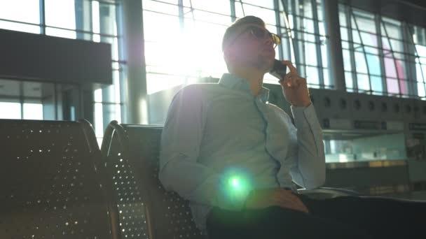 Mladý podnikatel mluví o telefonu na letišti s odlesk slunce na pozadí. Portrét pohledný podnikatel v sluneční brýle mluvit o mobilní telefon v kanceláři. Zpomalené Detailní záběr