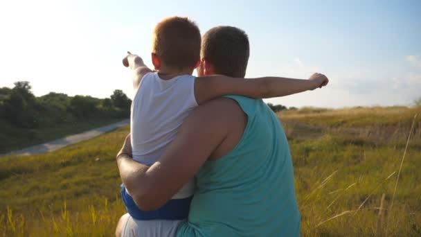 Otec se svým malým synem tráví společně čas venkovní. Táta a dítě sedí na kopci u zelené trávy a ukazoval na něco. Detailní záběr Zpomalený pohyb zadní zadní pohled