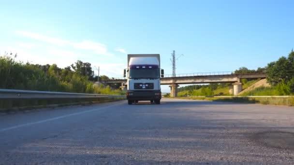weißer LKW, der auf einer Autobahn fährt. LKW fährt durch die Landschaft mit wunderschöner Landschaft im Hintergrund. Zeitlupe Frontansicht