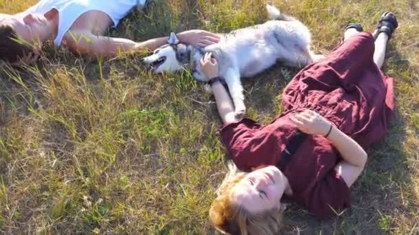 Dolly Schuss glückliches Paar auf Grün liegen im Bereich Rasen und streicheln ihre Siberian Husky Hund am sonnigen Tag. Junges Paar in Liebe entspannen und Sommerwochenende bei Sonnenuntergang zu genießen. Ansicht von oben hautnah