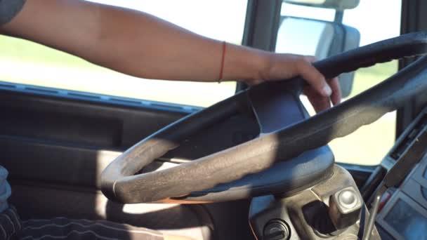 ARM řidič kamionu na kormidlo, jak je cca. Mužské ruky držící velký volant při jednotky náklaďák. TRUCKER uvnitř nákladního auta. Uzavřete boční pohled Zpomalený pohyb