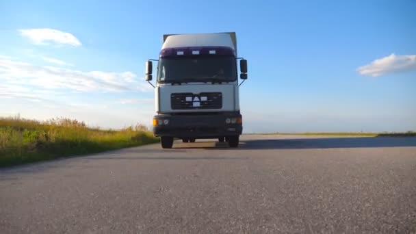 Kamera sleduje kamionu na dálnici. Nákladní automobil projíždí krajinou s krásnou krajinou v pozadí. Spodní boční pohled Zpomalený pohyb