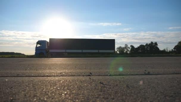 Kamiony na dálnici. Nákladní automobil projíždí krajinou s krásnou krajinou v pozadí. Zpomalený pohyb dolní boční pohled