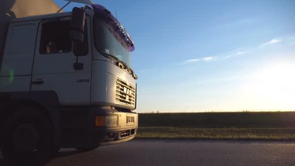 Auto na dálnici v večer. Sluneční světlo dopadá na řidičovy kabiny. Nákladní automobil projíždí krajinou s krásnou krajinou v pozadí. Boční pohled zpomalené Detailní záběr