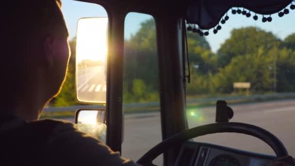 Muž jízdy kamionu a pečlivě sledovat silnici. Kavkazská chlap je na koni krajinou s krásnou krajinou v pozadí. Profil z řidiče uvnitř kabiny. Zpomalené Detailní záběr