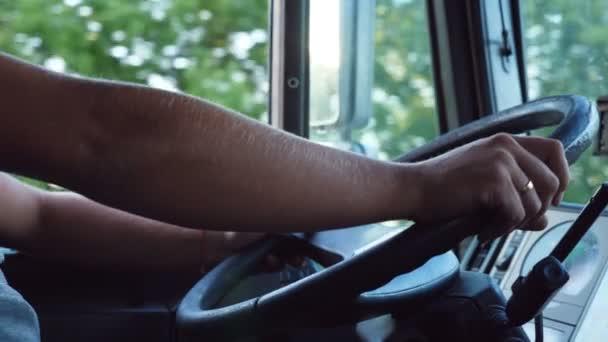 K nepoznání muž držel ruce na volant a řídit auto na polní cestě na teplý letní den. Řidič náklaďáku jezdí do cíle. Pohled z kabiny nákladního automobilu. Zpomalené Detailní záběr