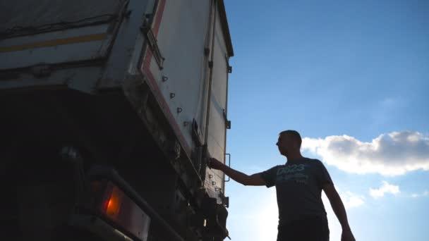 Řidič přichází k přívěsu kamionu a otevře dveře. Nákladní auto zaparkované v přírodě. Krásná krajina na pozadí. Spodní pohled zpomalené Detailní záběr