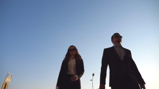 Obchodní muž a žena bude na letiště se svými zavazadly. Mladý podnikatel kufrem na kolečkách a chodí s jeho kolegyně do odbavovací haly. Výlet nebo cestování konceptu Slow motion