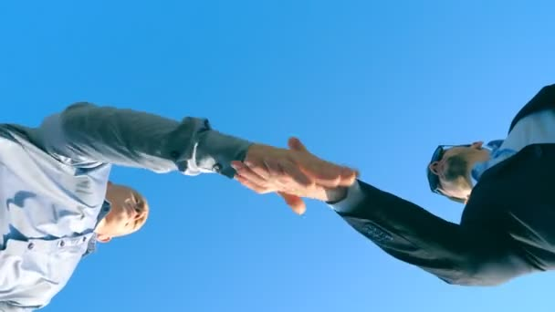 Young salesman in formal suit greeting with male buyer and giving him keys of car on the blue sky background. Handshake between two businessmen. Concept of selling and buying transport. Low angle view