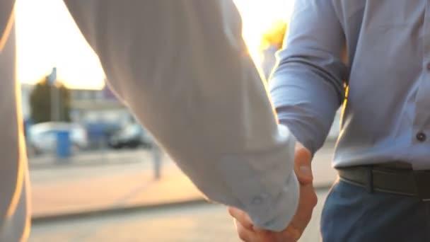 Dolly výstřel dvou mladých kolegů, setkání a potřesení rukou na městské ulici na západ slunce. Úspěšní podnikatelé navzájem pozdrav na pozadí parkoviště automobilů. Obchodní handshake venkovní