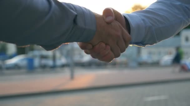 Detailní záběr ze dvou úspěšných podnikatelů navzájem pozdrav na pozadí parkoviště automobilů. Mladí kolegové setkání a potřesení rukou na městské ulici na západ slunce. Obchodní handshake venkovní
