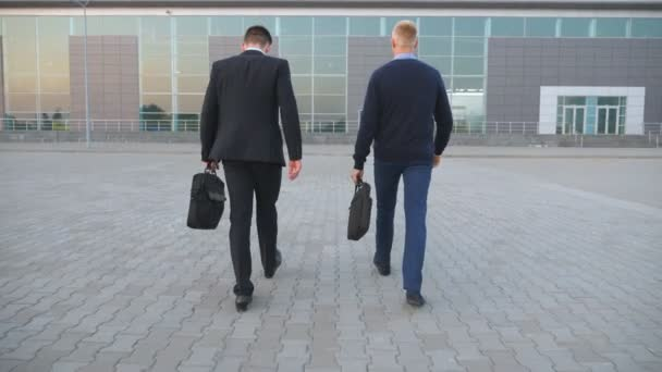 Two unrecognizable young businessmen in formal wear going with briefcases to office center. Confident managers going with bags to job in city. Successful colleagues commuting to work. Rear view