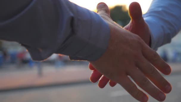 Two successful businessmen greeting each other against the background of cars parking. Young colleagues meeting and shaking hands at city street on sunset. Business handshake outdoor. Slow motion