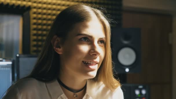Portrait of beautiful girl singing in sound studio. Young singer emotionally sings song. Working of creative musician. Show business concept. Slow motion Close up