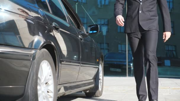 Geschäftsmann kommt zum Auto und öffnet der schönen jungen Frau die Tür. Mann entdeckt Autotür für Beifahrerin Mädchen steigt aus dem Auto und geht mit ihrem Freund. Zeitlupe