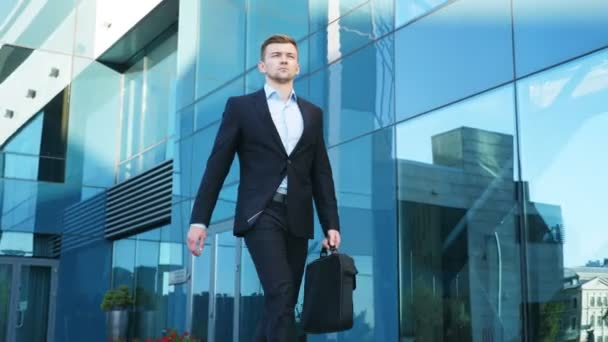 Young businessman with a briefcase walking in city street near modern office building. Confident guy in suit being on his way to job. Portrait of business man commuting to work. Slow motion Close up