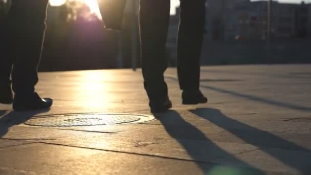 Feet of two businessmen walking in city street with sun flare at background. Business men commute to work together. Confident guys being on his way to office. Colleagues going outdoor. Slow motion