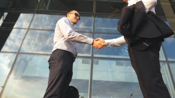 Dva obchodníci se scházejí poblíž kancelářské budovy a zdraví se. Obchodní handshake venkovní v městském prostředí. Potřesení mužských paží venku. Kolegové si podávají ruce. Zavřít Zpomalený pohyb