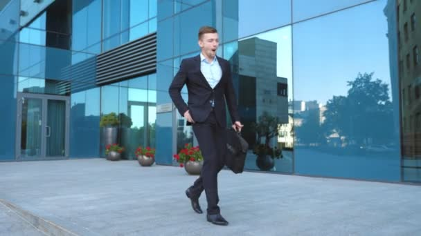 Business man heard good news on cellphone and having positive emotions. Portrait of guy is happy with success. Young businessman talking on phone near office and celebrating achievement. Slow motion