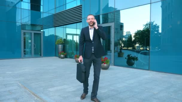 Portrait of guy is happy with success. Business man heard good news on cellphone and having positive emotions. Young businessman talking on phone near office and celebrating achievement. Slow motion