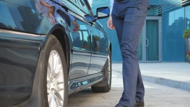 Fahrer kommt zum Auto und öffnet Tür für Geschäftsmann. Chauffeur deckt Autotür für männlichen Beifahrer auf Geschäftsmann mit Aktentasche steigt aus dem Auto und geht zum Bürogebäude. Zeitlupe