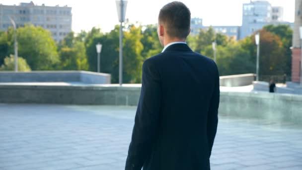 Mladý podnikatel s Aktovkou chůzi ve městě. Nelze rozpoznat obchodní muž dojíždění do práce. Jistý chlap v obleku je na cestě do práce. Panorama v pozadí. Zpomalený pohyb zadní pohled