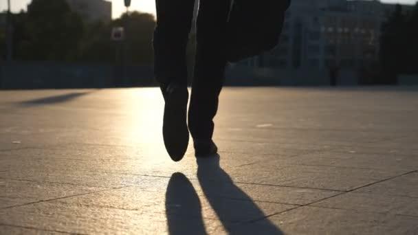 Nohy mladý podnikatel s Aktovkou chůzi ve městě. Obchodní muž dojíždění do práce. Jistý chlap v obleku je na cestě do práce. Panoráma města pozadí. Zpomalený pohyb zadní pohled zblízka