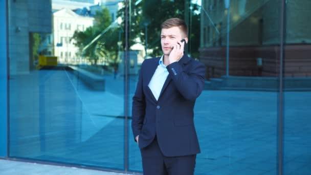 Pohledný podnikatel mluví o telefonu poblíž kanceláře a slaví úspěch. Mladý podnikatel slyšet dobré zprávy na mobil a mají pozitivní emoce. Portrét chlap je spokojený s úspěchem