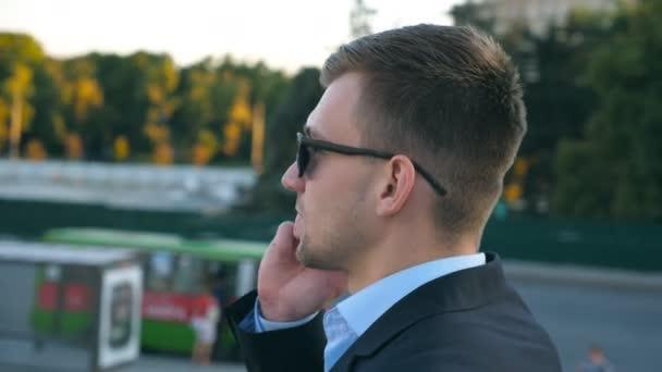 306e1213b8 Cámara girando alrededor del guapo empresario hablando por teléfono al aire  libre. Hombre de negocios joven en gafas de sol tener conversación en el ...